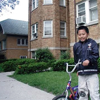 Boy with bike standing in front of an apartment